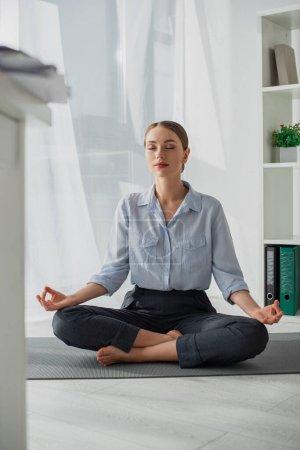 Photo pour Attrayant femme d'affaires pratiquant le yoga en position lotus avec mudra gyan sur tapis au bureau - image libre de droit