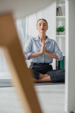 Photo pour Foyer sélectif de la femme d'affaires pratiquant le yoga en position lotus avec geste namaste sur tapis dans le bureau - image libre de droit
