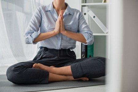 Photo pour Vue recadrée de femme d'affaires pratiquant le yoga en position lotus avec geste namaste sur tapis au bureau - image libre de droit