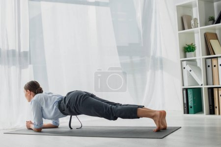 Photo for Beautiful businesswoman practicing yoga in plank on mat in office - Royalty Free Image