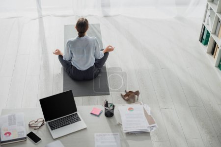 Photo for Back view of businesswoman practicing yoga in lotus position with gyan mudra on mat in office with laptop - Royalty Free Image