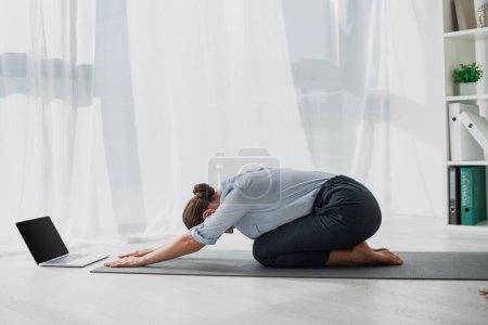 Photo pour Jeune femme d'affaires dans Child Pose ayant des cours de yoga en ligne sur ordinateur portable au bureau - image libre de droit