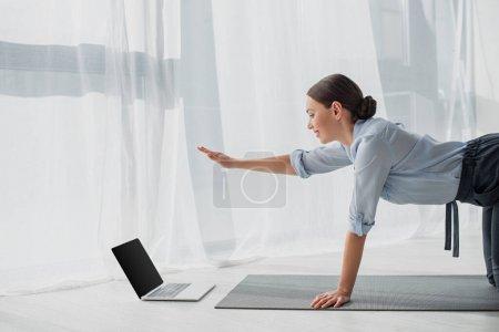 Photo pour Souriant femme d'affaires ayant des cours en ligne sur ordinateur portable et pratiquant le yoga dans la pose de chien oiseau sur tapis au bureau - image libre de droit