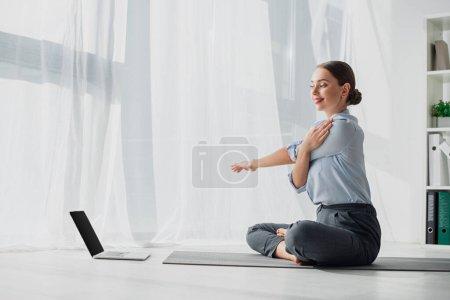 Photo pour Jeune femme d'affaires ayant des cours en ligne sur ordinateur portable et étirant les mains en position lotus sur tapis dans le bureau - image libre de droit