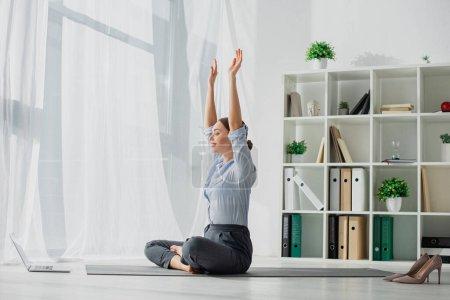 Photo pour Jeune femme d'affaires ayant des cours en ligne sur ordinateur portable et pratiquant le yoga en position lotus sur tapis avec les mains en l'air au bureau - image libre de droit