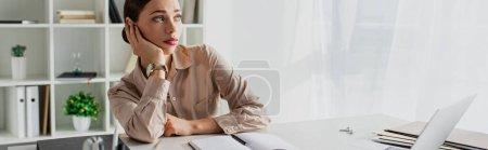 Photo pour Plan panoramique de femme d'affaires ennuyée travaillant avec un ordinateur portable dans un bureau moderne - image libre de droit