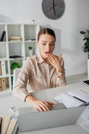 Photo pour Surpris femme d'affaires attrayante travaillant avec un ordinateur portable dans un bureau moderne - image libre de droit