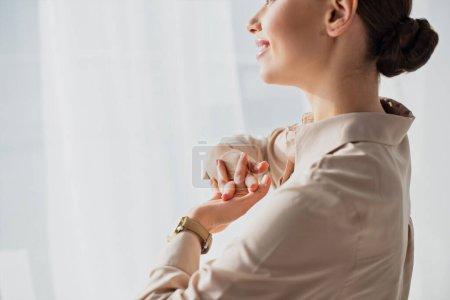 recortado vista de sonriente mujer de negocios estirando las manos en la oficina