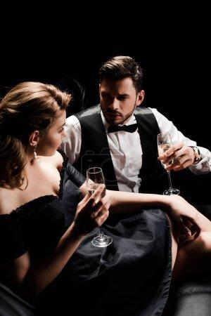 Photo pour Élégant homme et femme tenant des verres de champagne et se regardant tout en étant assis isolé sur noir - image libre de droit