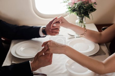 Photo for Cropped view of man and woman holding hands while sitting at served table in plane - Royalty Free Image