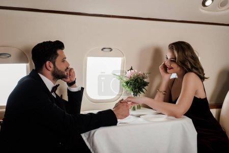 Photo pour Élégant homme et femme tenant la main tout en étant assis à la table servie dans l'avion - image libre de droit