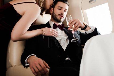 Photo pour Vue recadrée d'une femme séduisante touchant un homme élégant et confiant tenant un verre de champagne - image libre de droit