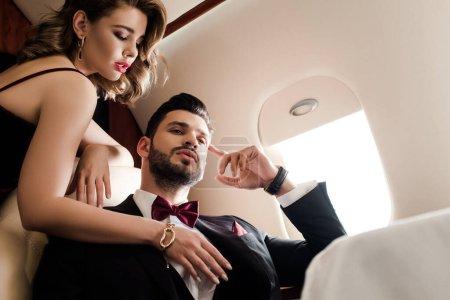 Photo pour Vue à angle bas de femme sexy toucher la poitrine de l'homme élégant et confiant dans l'avion - image libre de droit