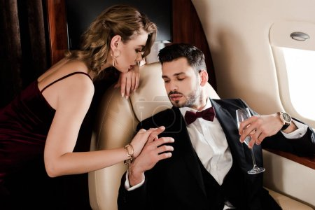 Photo for Seductive woman touching elegant man holding glass of champagne in plane - Royalty Free Image
