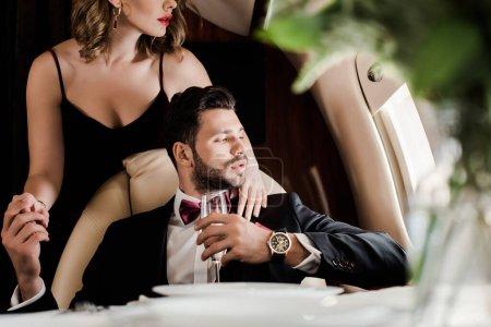 Foto de Vista recortada de la mujer sexy tocando elegante hombre sosteniendo la copa de champán en avión - Imagen libre de derechos