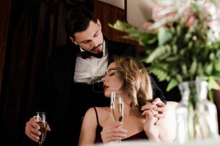 Photo pour Foyer sélectif de couple élégant tenant des verres à champagne dans l'avion - image libre de droit