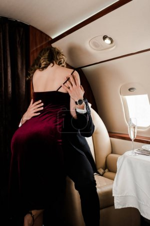 Photo for Back view of seductive woman hugging and kissing man in plane - Royalty Free Image