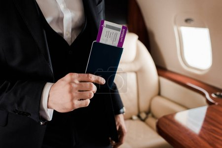 Photo for Partial view of elegant man holding passport and air tickets in plane - Royalty Free Image