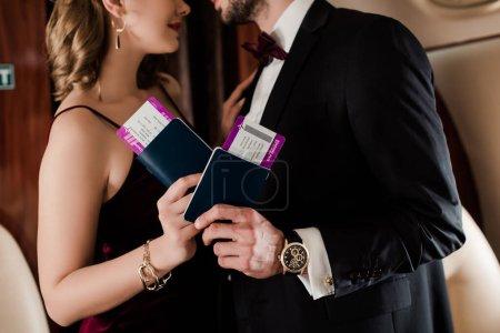 Photo pour Vue recadrée du couple élégant tenant passeport et billet d'avion dans l'avion - image libre de droit