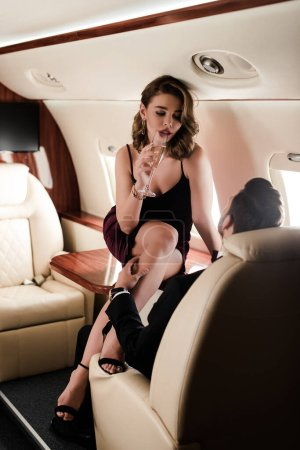 Photo pour Femme passionnée avec verre de champagne assis sur la table dans l'avion tandis que l'homme touchant sa jambe - image libre de droit