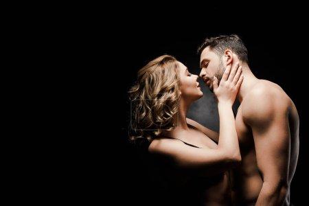 Photo pour Vue latérale de la fille sensuelle toucher le visage du petit ami sexy sur fond noir - image libre de droit