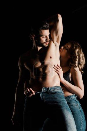 verführerisches Mädchen knöpft Jeans von sexy Freund isoliert auf schwarz auf