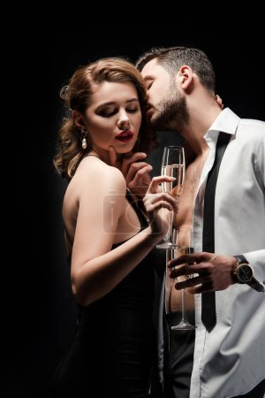 Photo pour Homme sexy en chemise déboutonnée embrasser élégant, passionné fille tenant verre de champagne isolé sur noir - image libre de droit