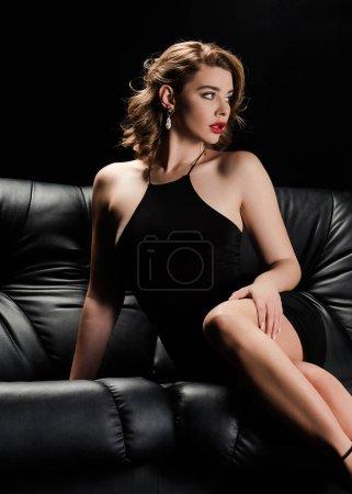 Photo pour Femme confiante, séduisante en robe élégante assise sur un canapé en cuir et regardant loin isolée sur le noir - image libre de droit