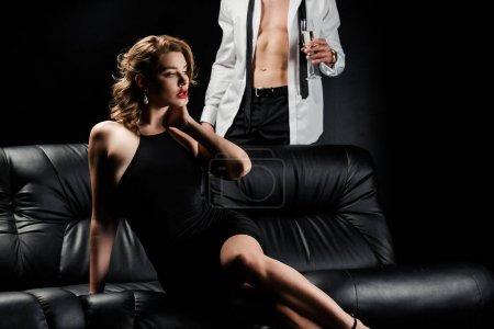 Photo pour Vue recadrée de l'homme sexy en chemise déboutonnée tenant verre de champagne près de femme séduisante assise sur un canapé en cuir sur fond noir - image libre de droit