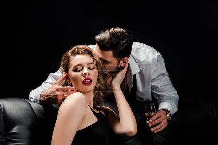 Photo pour Bel homme tenant verre de champagne et embrassant femme séduisante assise sur canapé isolé sur noir - image libre de droit