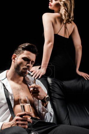 cropped view of sensual girl sitting on back of sofa near confident, sexy man holding champagne glass and smoking isolated on black