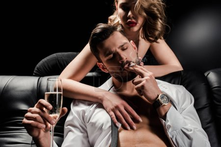 Photo for Sexy woman touching handsome, confident man sitting on sofa with champagne glass and smoking on black background - Royalty Free Image