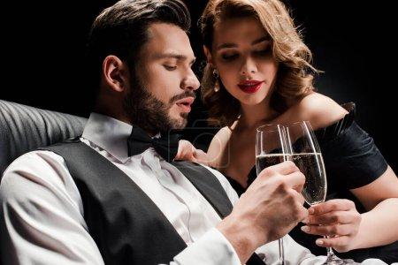 Photo pour Attrayant femme et élégant homme cliquetis verres de champagne isolé sur noir - image libre de droit