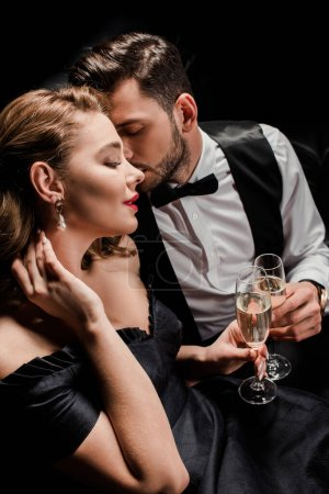 stylish, seductive woman and elegant man clinking glasses of champagne isolated on black