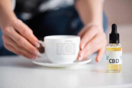 Photo for Cropped view of mature woman touching cup of tea near bottle with cbd lettering - Royalty Free Image
