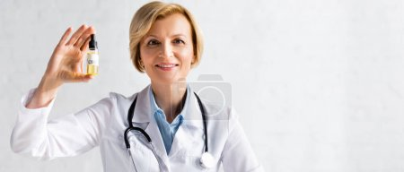 Photo for Panoramic shot of happy and mature doctor in white coat holding bottle with oil and cbd lettering in clinic - Royalty Free Image