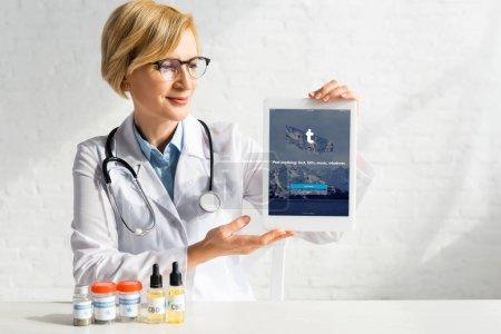 Photo pour KYIV, UKRAINE - 5 MARS 2020 : médecin adulte en manteau blanc tenant une tablette numérique avec application tumblr près de bouteilles avec cbd et lettrage de cannabis médical - image libre de droit