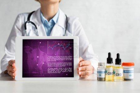 Foto de Visión aproximada de los médicos maduros que tienen tableta digital con aplicación médica cerca de botellas con letras cbd. - Imagen libre de derechos
