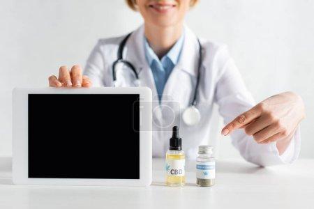 Photo pour Vue recadrée d'un médecin heureux et mature tenant une tablette numérique avec écran vierge et pointant du doigt les bouteilles avec du cbd et du lettrage de cannabis médical - image libre de droit