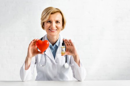 Photo for Cheerful and mature doctor holding bottle with cbd lettering and red heart in clinic - Royalty Free Image