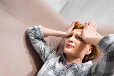 mujer madura que sufre de dolor de cabeza mientras está acostada en el sofá