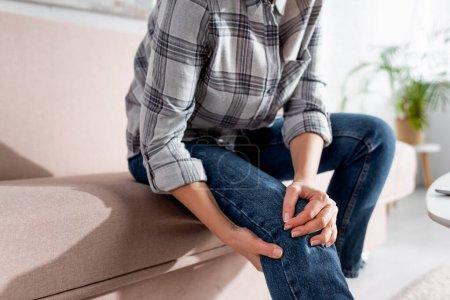 Photo pour Vue recadrée de la femme souffrant de douleur à la jambe tout en étant assis sur le canapé - image libre de droit