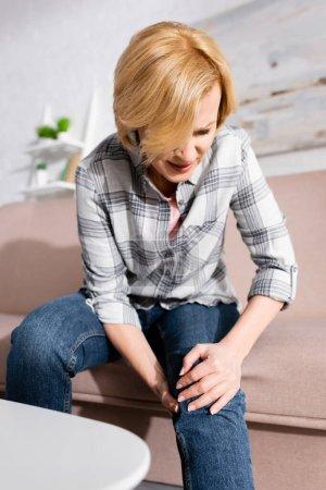 femme mûre souffrant de douleur dans la jambe tout en étant assis sur le canapé