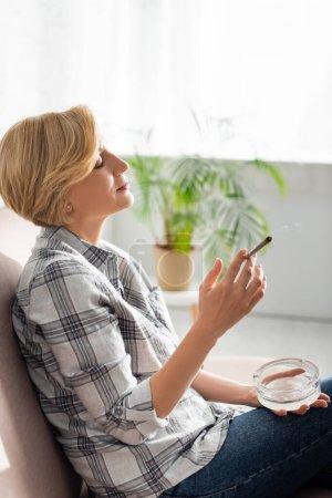 Photo pour Vue latérale de femme mature fumant joint avec de la marijuana légale et tenant cendrier - image libre de droit