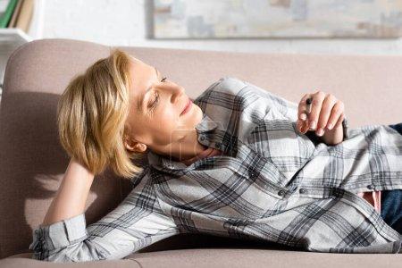 Photo pour Femme heureuse et mature couchée sur le canapé et tenant joint avec de la marijuana légale - image libre de droit