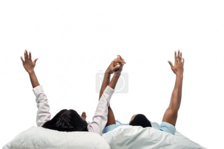african american couple lying in bed with hands in air in pajamas isolated on white