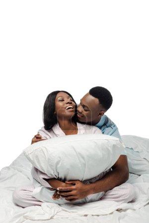 Photo pour Heureux couple afro-américain étreignant oreiller au lit en pyjama isolé sur blanc - image libre de droit