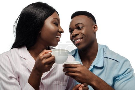Photo for Happy african american couple drinking coffee in pajamas isolated on white - Royalty Free Image