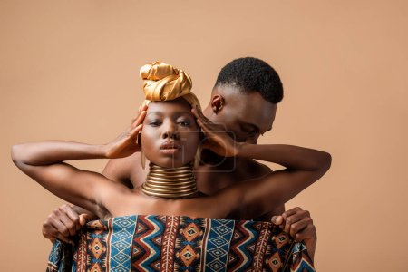 sexy naked tribal afro woman covered in blanket posing near man isolated on beige