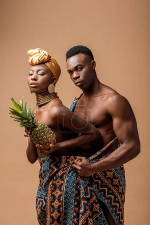 sexy naked tribal afro woman covered in blanket posing with pineapple near man isolated on beige